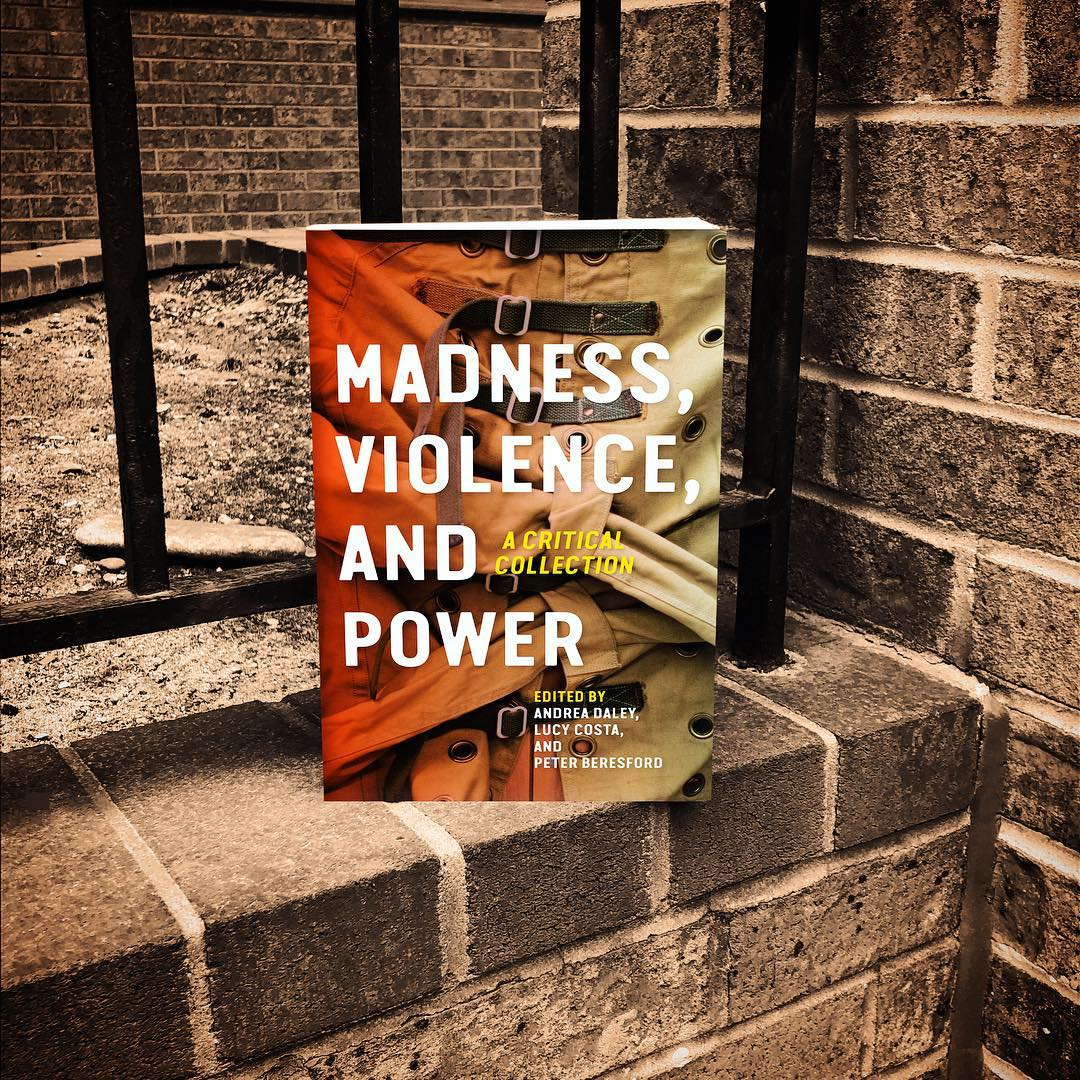 Book cover in front of brick wall.