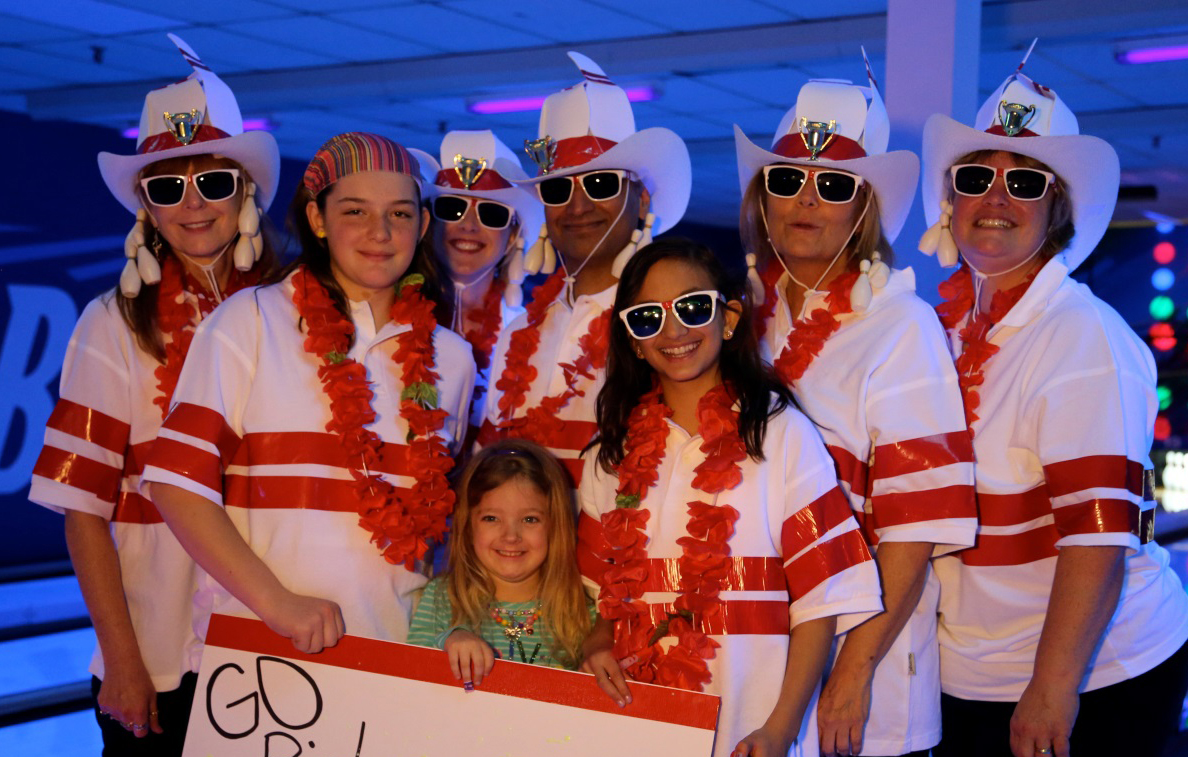 7 people dressed in fun hawaian themed outfits at a bowling alley