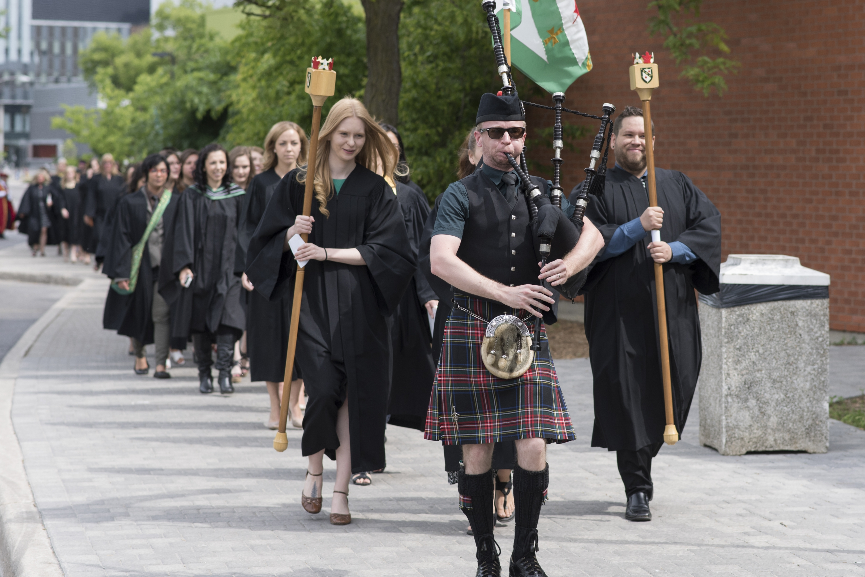 Line of Renison students following a piper from Hagey Hall at spring convocation