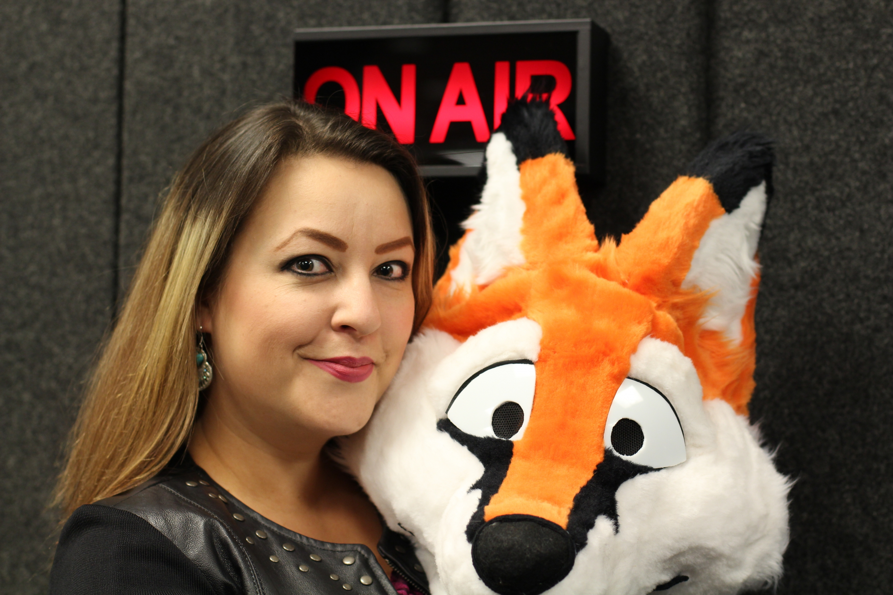 "Prof. Sharon Roberts with a fur suit head in front of an ""On Air"" sign"