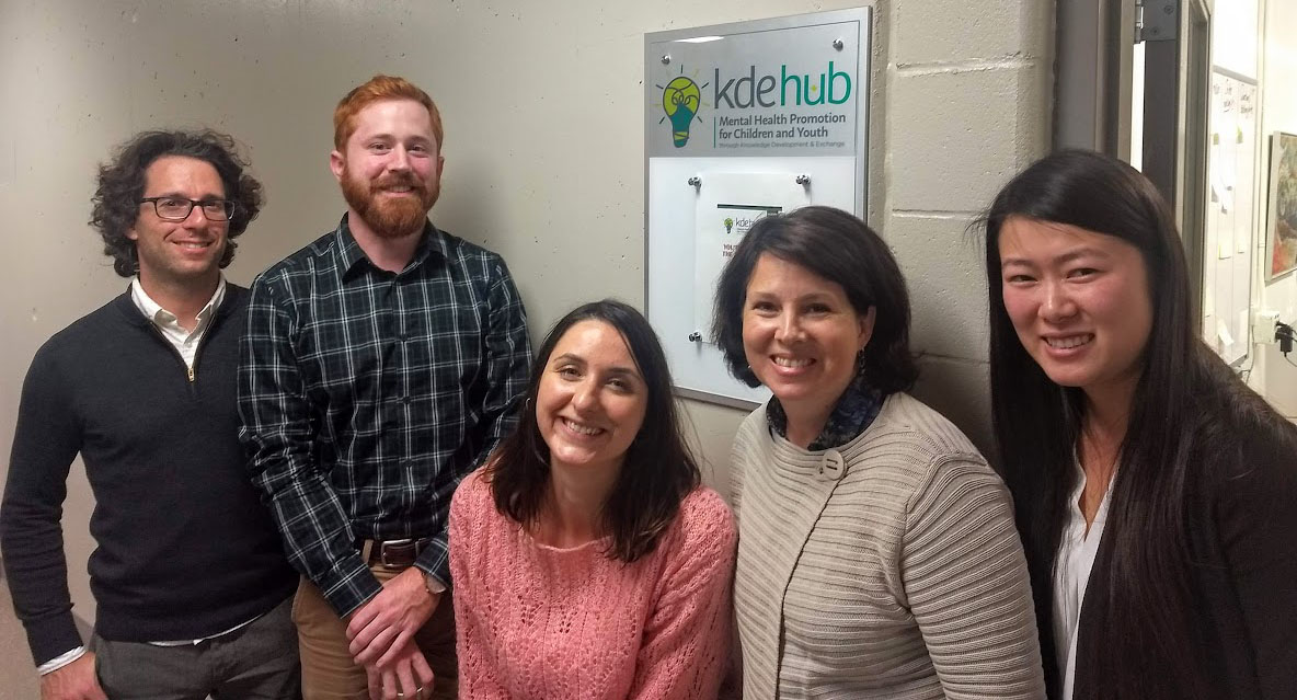 KDE Hub staff stand in front of their office door.