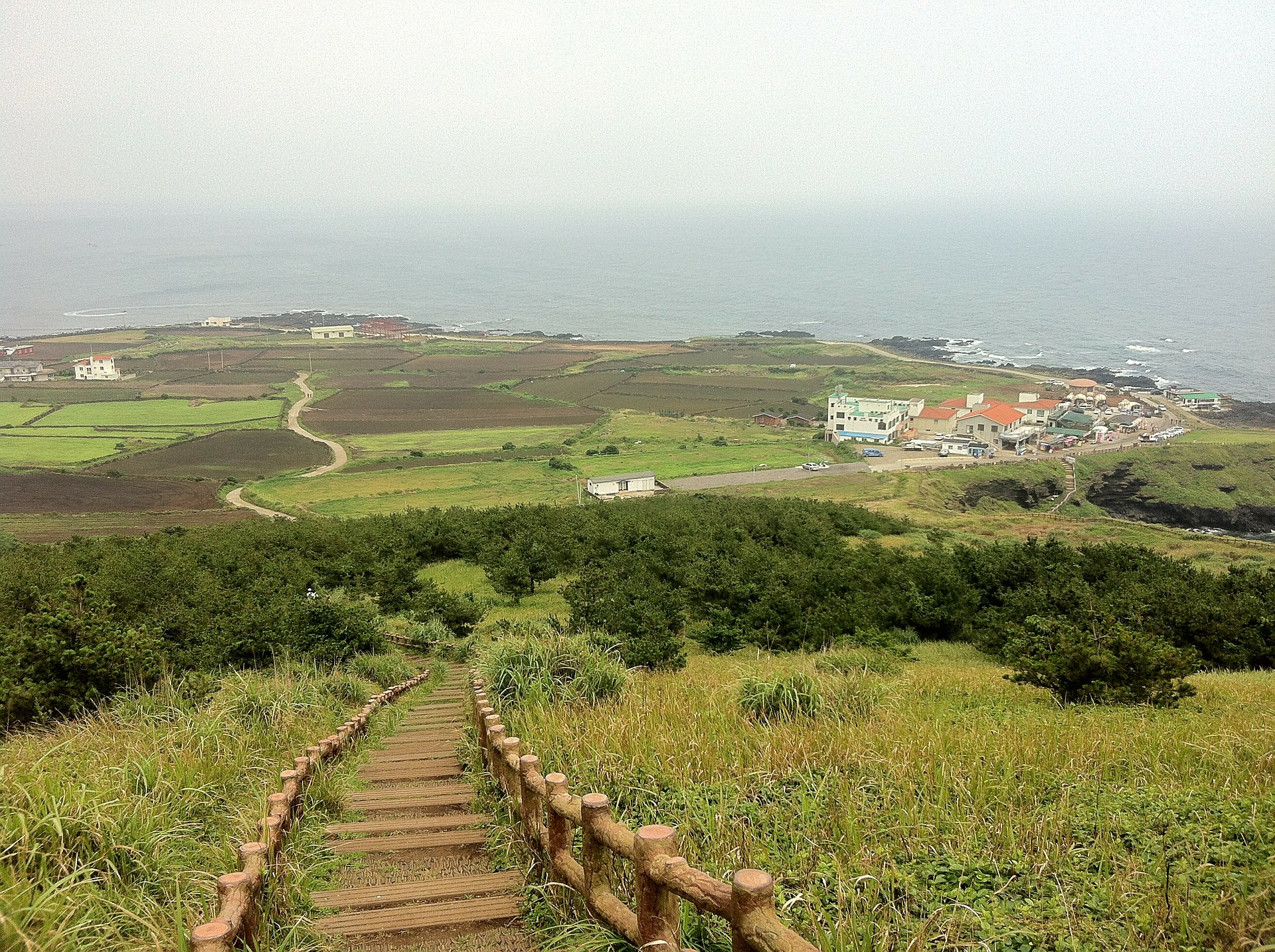 Landscape of Jeju island showing a walkway through the countryside.