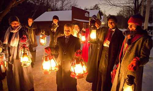 Guides dressed in winter clothing stand with lit lanterns