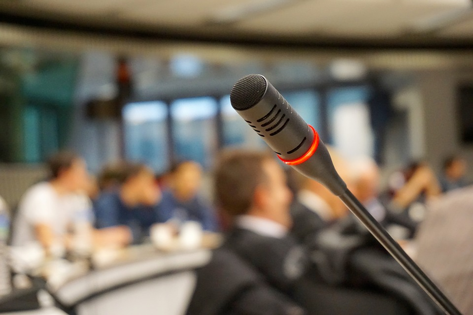 microphone on lecture stand with people seated in the background