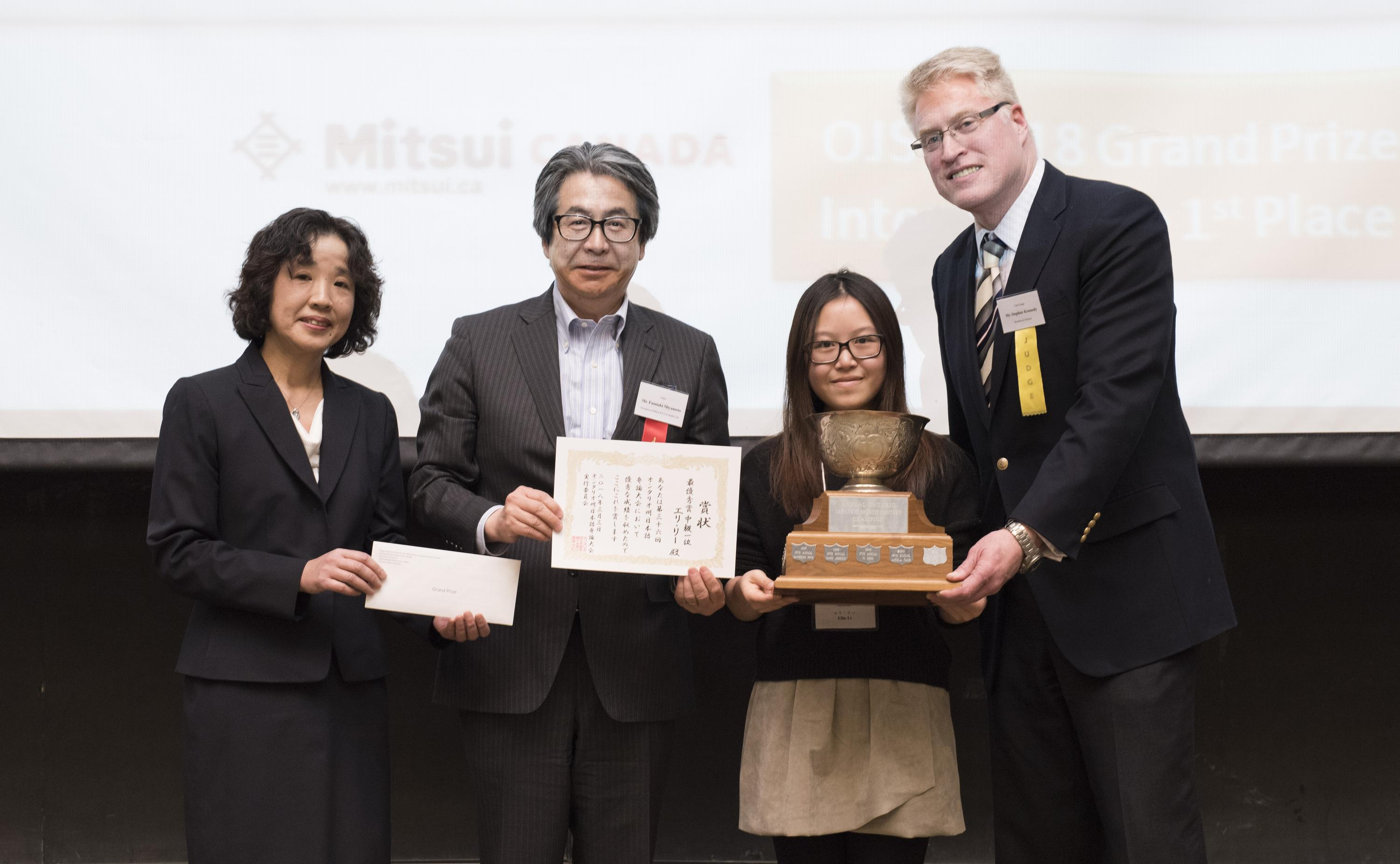 Ellie Li holds the Ontario Japanese Speech Contest trophy alongside contest officials