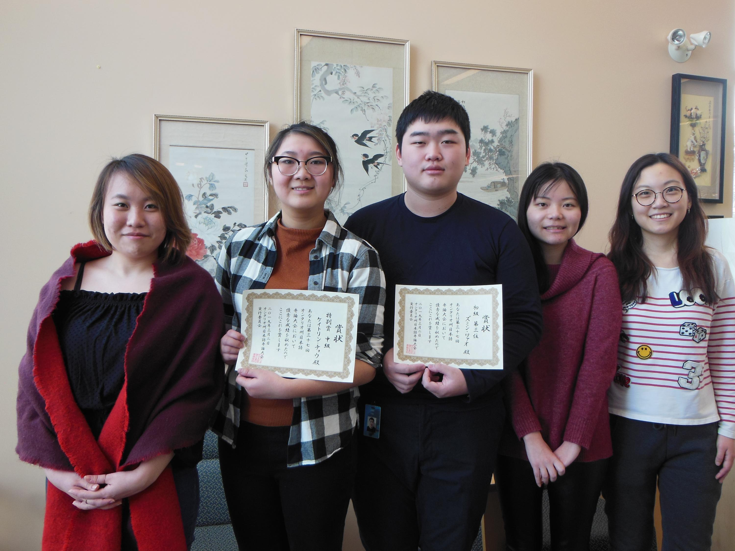 Five students standing in a row, two are their winning certificates.