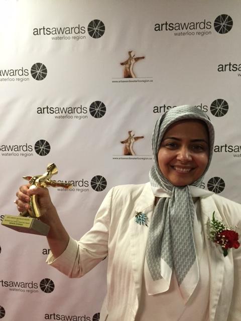 Soheila Esfahani holds up Arts Awards Waterloo Region trophy