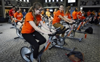 students ride stationary bikes for mental health wellness day