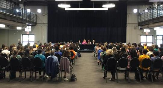 Four women speaking on a panel to a large audience