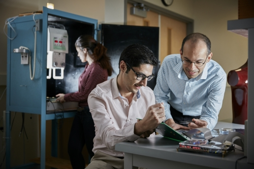 Waterloo Professor Karim S. Karim (right) and PhD student Sina Ghanbarzadeh examine the electronics test board for Karim's prototype X-ray imager while MASc student Saeedeh Ghaffari prepares the X-ray cabinet for imager characterization.