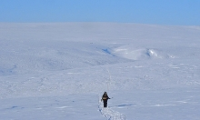 Researcher walking on snow covered land