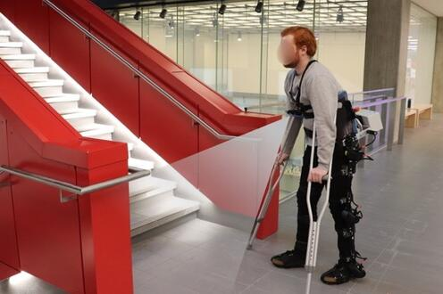 Bearded man using a lower-body exoskeleton and crutches with a chest-mounted camera near stairs