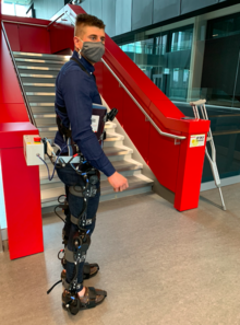 Brokoslaw Laschowski in an exoskeleton in front of stairs