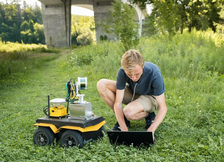 Stephen Phillips, a PhD student at the University of Waterloo, works with a robotic ground vehicle used in research on automatin