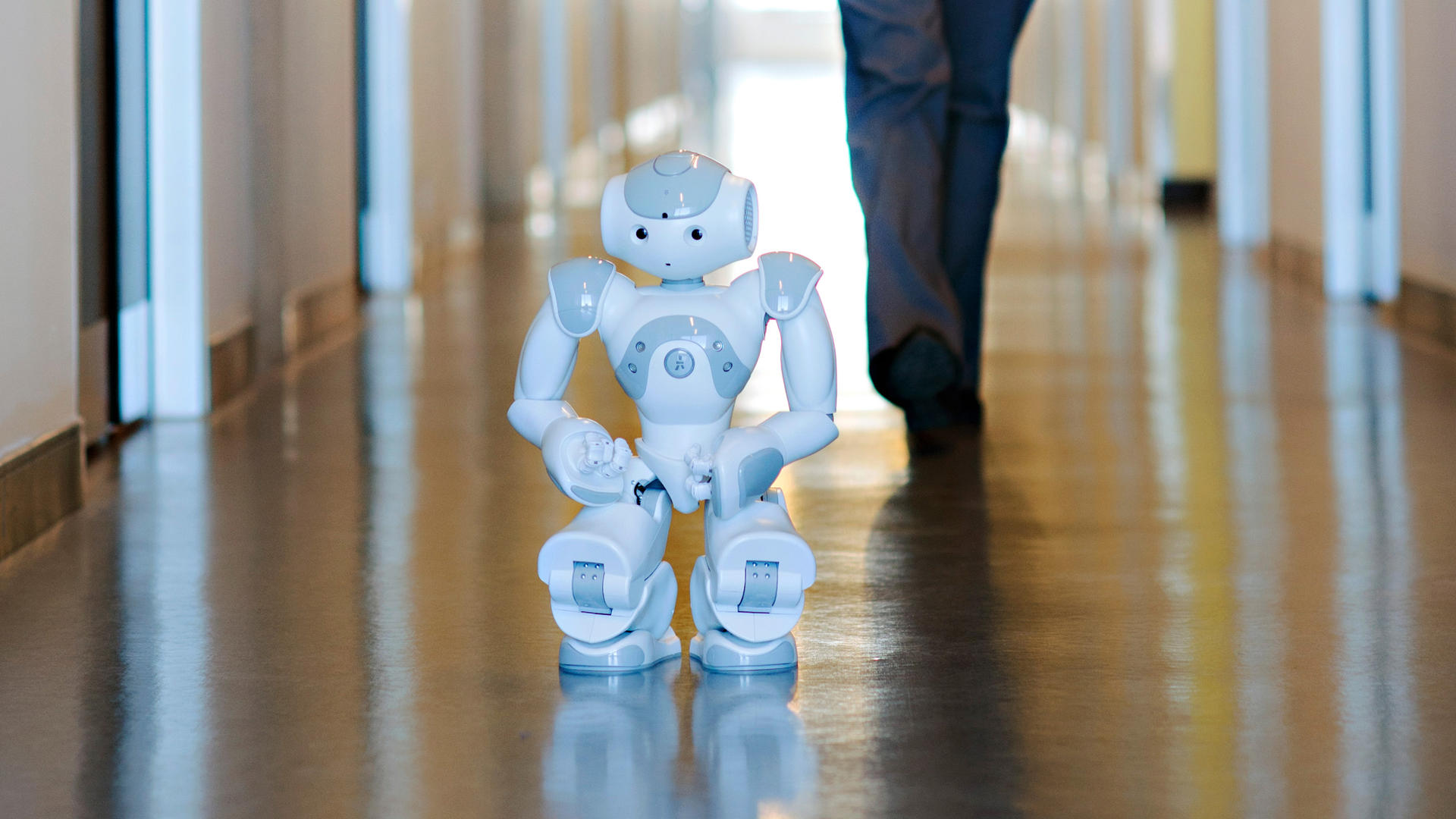 NAO robot crouching in a hallway