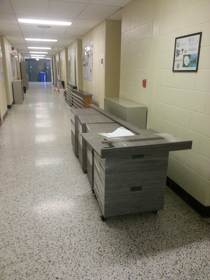 cabinets in hallway, ready to be installed in the new office