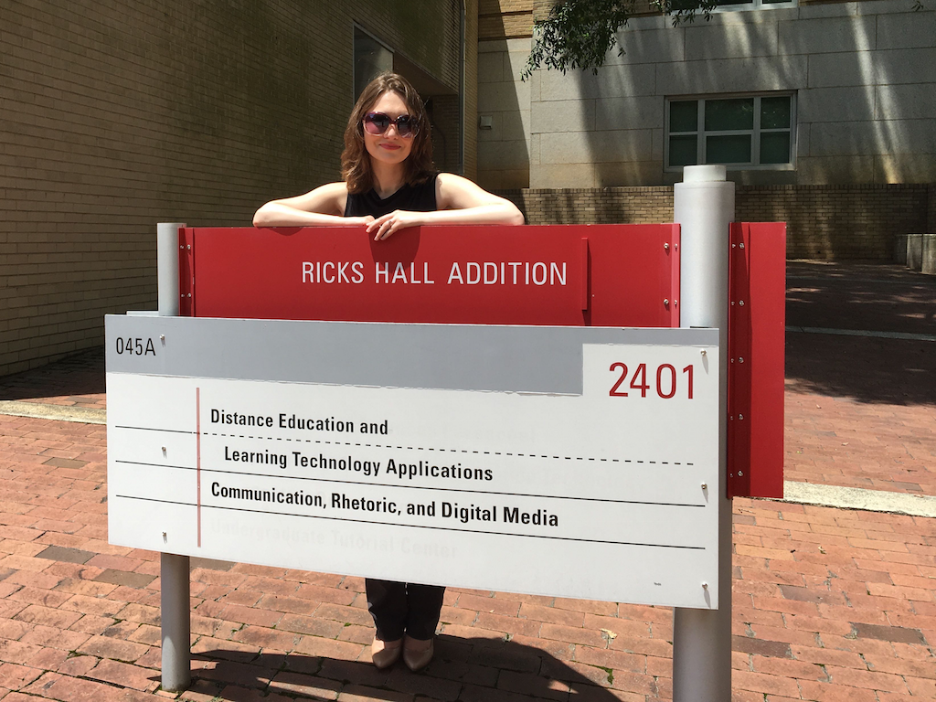 Ashley Rose Mehlenbacher looking at the camera while standing behind a sign for the Communication, Rhetoric, and Digital media program at NC State University