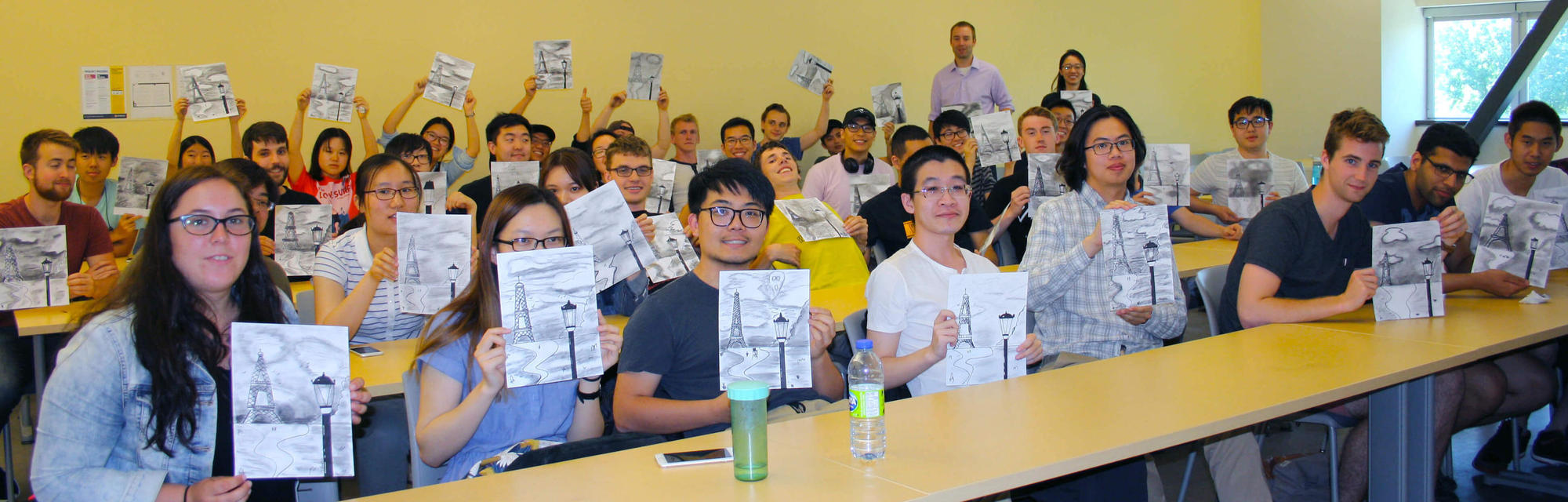 Students holding up their drawings