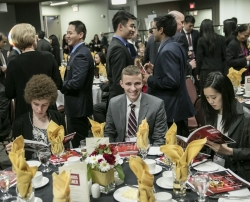 Students sitting at a table, with others in the background mingling