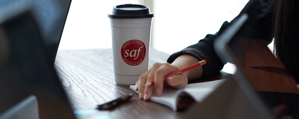 SAF mug, student holding pencil about to write