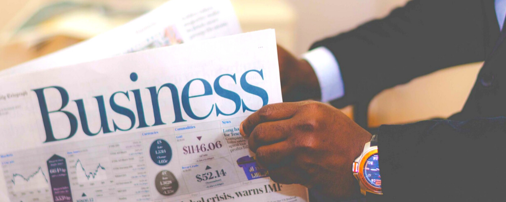 Person holding the business section of the newspaper