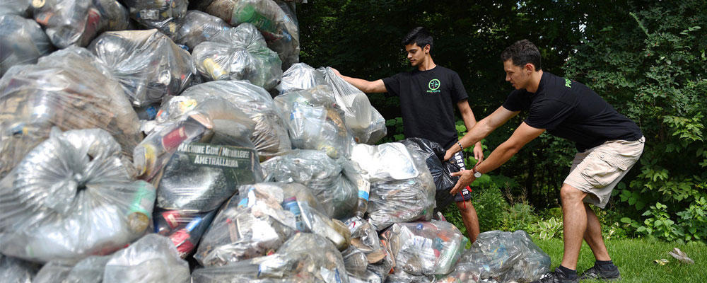 Two students pulling waste from a mountain of garbage bags