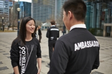 "2 students in black shirts with ""Ambassador"" printed on back chatting with each other."