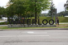 Kyrie with University of Waterloo sign, looking away.