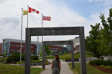 Kyrie standing near the University of Waterloo sign at Seagram Drive