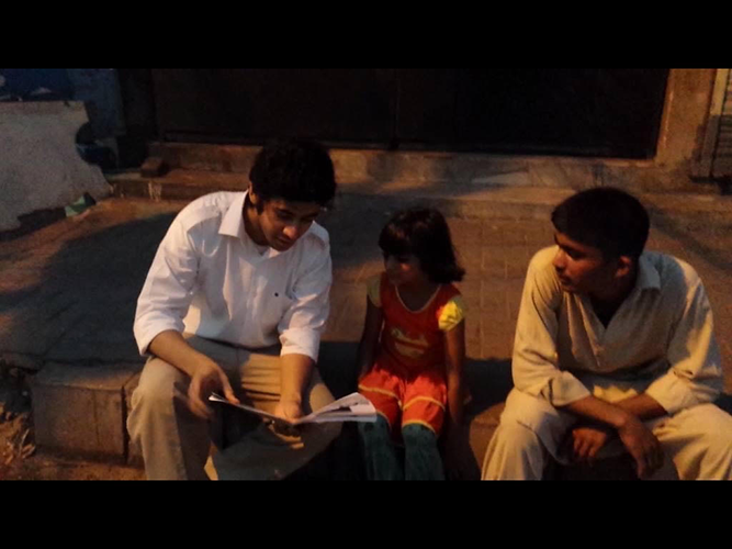 Photo of Shan and colleague teaching a student in Pakistan