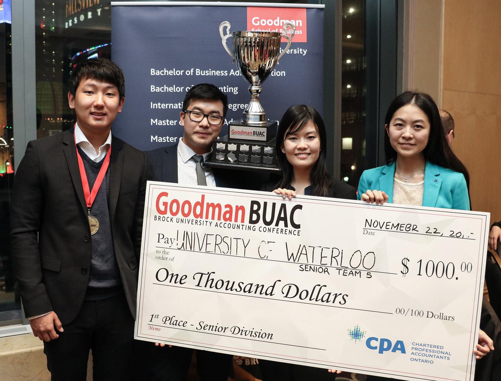 Student winners holding a big Goodman BUAC check