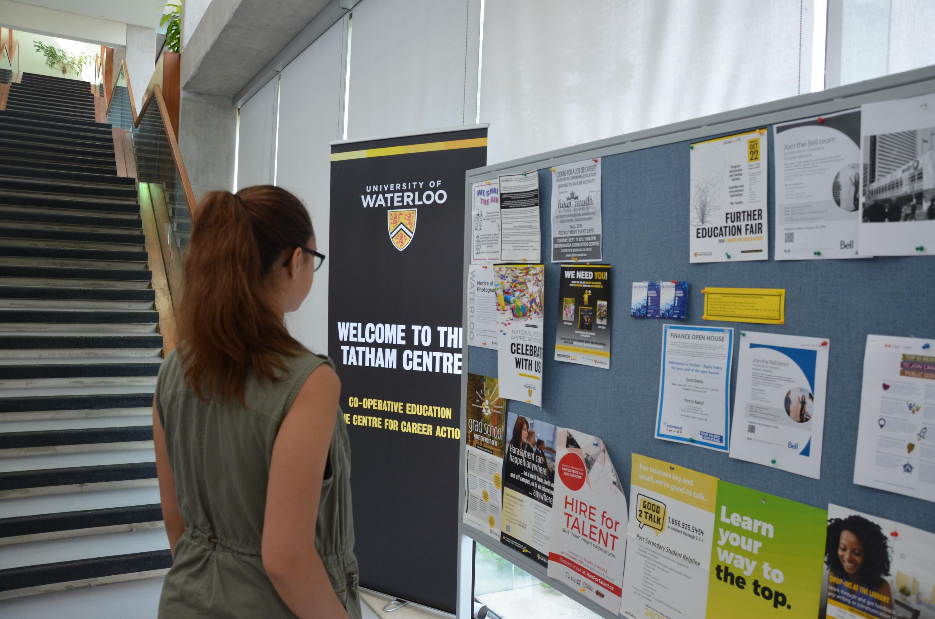 Kyrie looking at a bulletin board in the Tatham Centre
