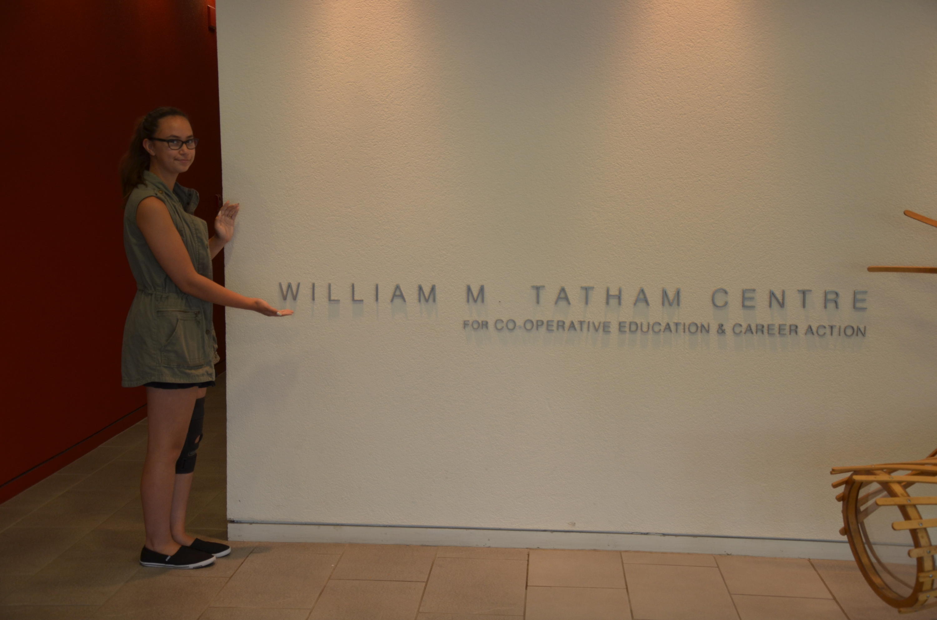 Kyrie at Tatham Centre standing beside the Tatham Centre sign
