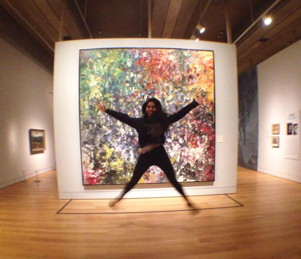 Qhalisa jumping in front of painting in a museum