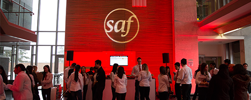 Photo of interior of School of Accounting and Finance with red lighting and ambassadors mingling.