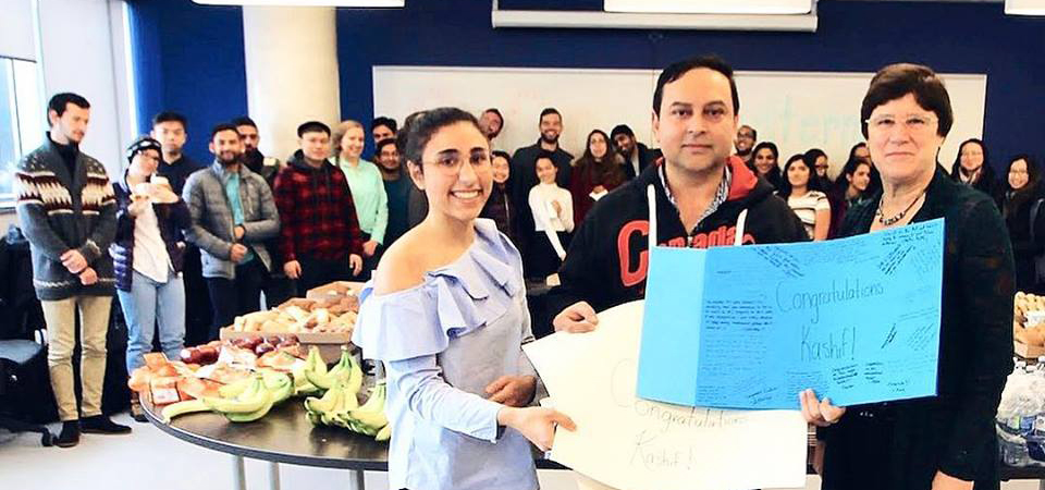 Science and Business students surround Kashif Memon who holds a card with a student and program director Jean Richardson.