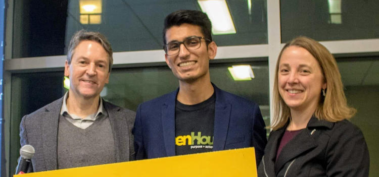A man, Manav Kainth and Tania Del Matto hold a large yellow congratulatory sign.