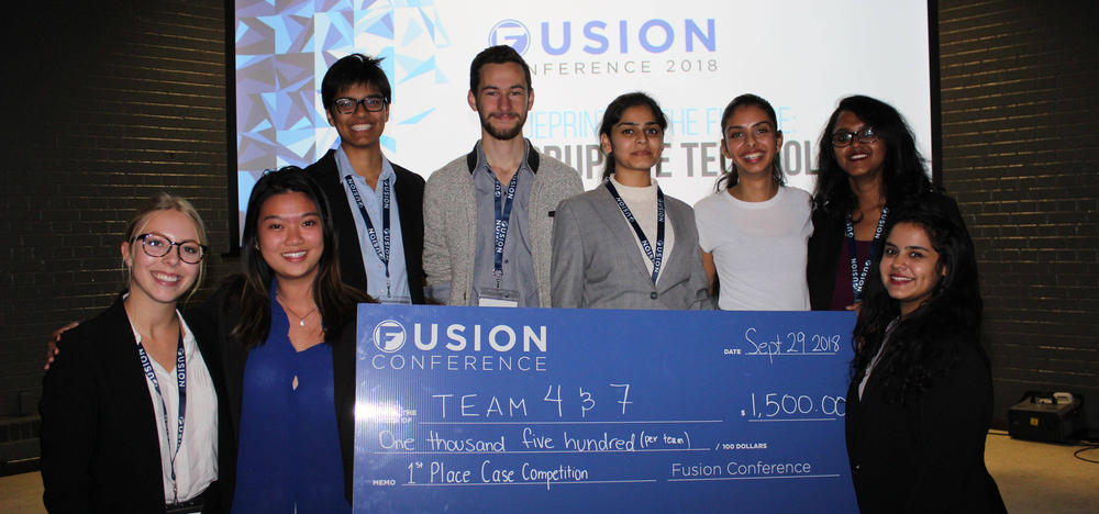 Student teams winning the Fusion Case competition hold a large blue cheque.