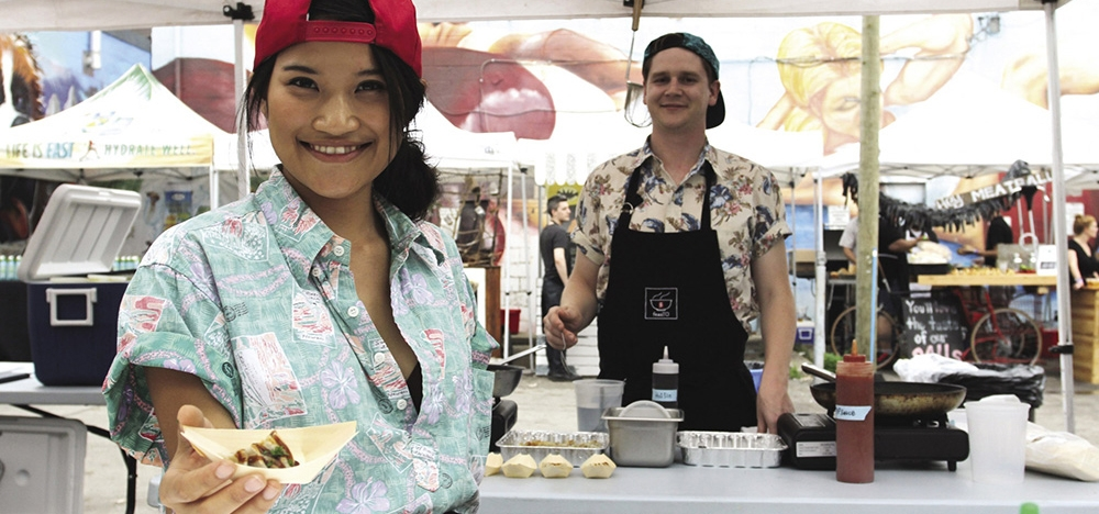 Ada Mok and Cameron Pounder serving food from their award winning food truck business.