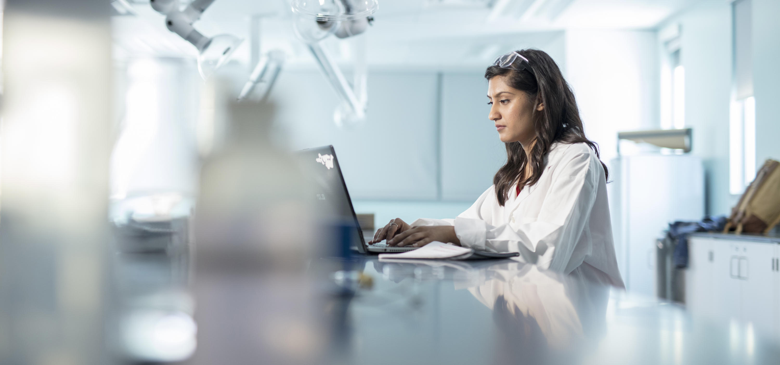 Female working on a computer while sitting at a lab bench.