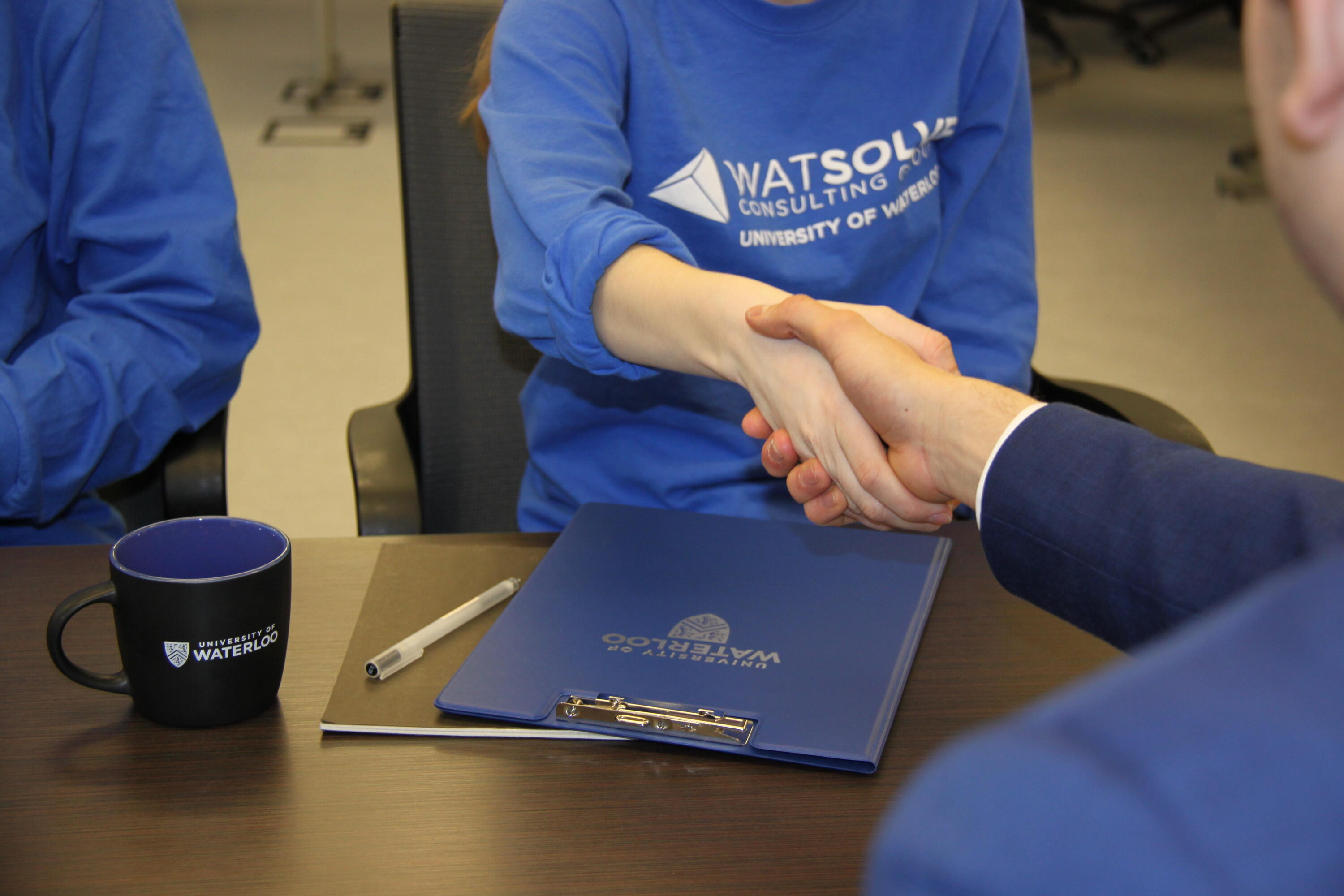 Handshake with blue Waterloo branded mug and notebook on the table.