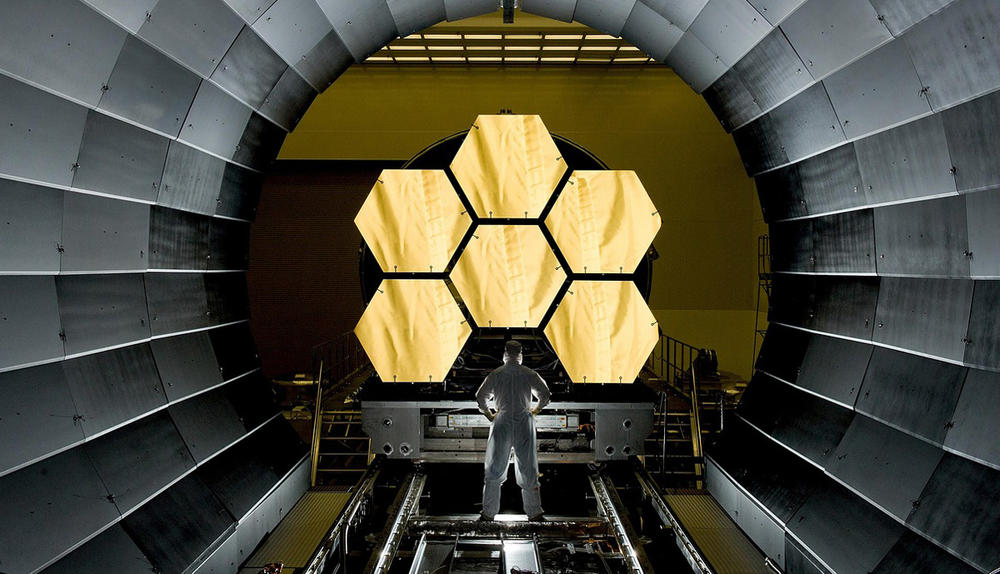 Scientist standing in front of space telescope