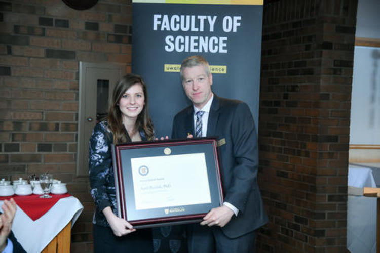 April Pawluk accepts a plaque from Hugh Broders
