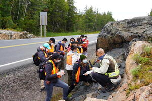 Group of students clustered around a rock outcrop at the side of the road. Instructor perched on the rock, talking with 2 students, and the rest are looking at the rock