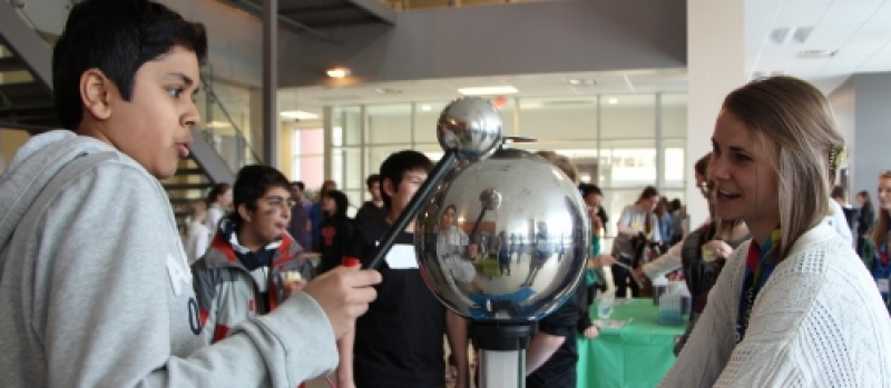 student tries out the van de Graaf generator with volunteer