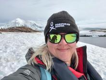 Kirsten Müller in Port Lockroy, Antarctica with gentoo penguins in background