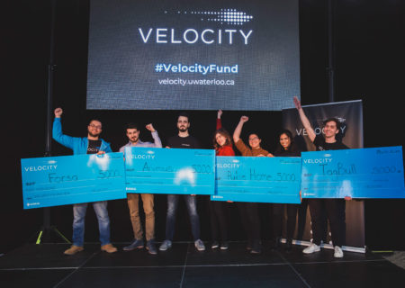 Four Velocity Fund $5K competition winners holding their cheques.