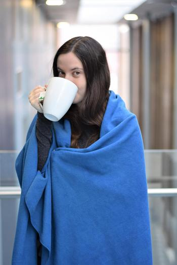 Becca wrapped in a blanket and drinking tea out of a mug