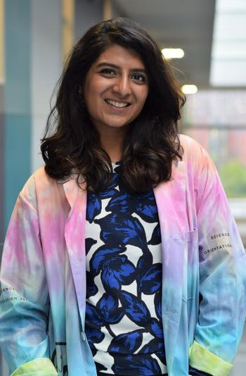 Divya smiling while wearing her colourful orientation week lab coat