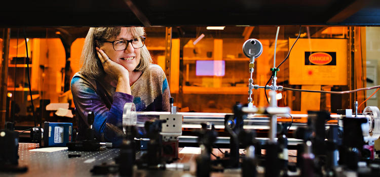 Donna Strickland sitting at a table of optics in her lab.